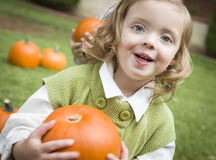 Cure Young Child Girl Enjoying the Pumpkin Patch. Royalty Free Stock Photography
