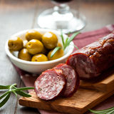 Cured dry sausage on chopping board Royalty Free Stock Images