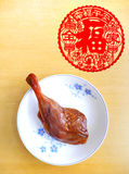 Cured duck leg, chinese festive food. A photograph showing a cured and salted duck leg drum stick on an oriental motif plate with a red festive lunar new year Royalty Free Stock Photos