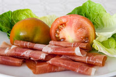 Cured ham, tomatoes and lettuce, close-up. Plate with cured ham, tomatoes and lettuce Royalty Free Stock Photos