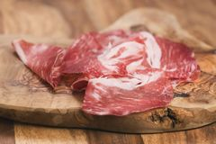Cured italian coppa on olive wood board. Shallow focus Stock Images