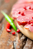 Cured meat with chilli pepper on wooden table Stock Image