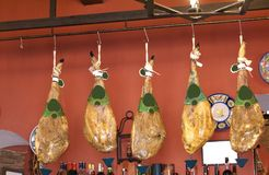Cured meat hanging from meat hooks on a rail Royalty Free Stock Images