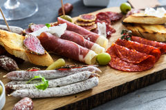 Cured meat platter of traditional Spanish tapas - chorizo, salsichon, jamon serrano, lomo - erved on wooden board with Royalty Free Stock Photo