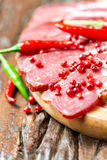 Cured meat with red chilli pepper on wooden table Royalty Free Stock Images