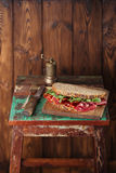 Cured meat sandwich with seeded bread on old wooden table Stock Photo