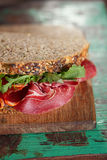 Cured meat sandwich with seeded bread on old wooden table. Shallow dof Stock Photography