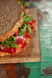 Cured meat sandwich with seeded bread on old wooden table Stock Photos