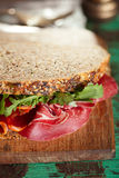 Cured meat sandwich with seeded bread on old wooden table Royalty Free Stock Images