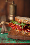 Cured meat sandwich with seeded bread on old wooden table Royalty Free Stock Photo