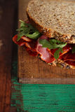 Cured meat sandwich with seeded bread on old wooden table Royalty Free Stock Photos