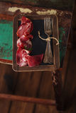Cured Meat and vintage forks on textured Chalkboard and old wood Stock Photo