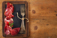 Cured Meat and vintage forks on textured Chalkboard and old wood Royalty Free Stock Photography