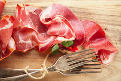 Cured Meat and vintage forks on textured  wooden background Royalty Free Stock Photos