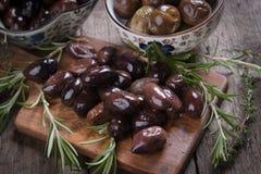 Cured greek olives. Cured, pickled or brined olive fruit on wooden table Stock Images