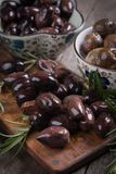 Cured greek olives. Cured, pickled or brined olive fruit on wooden table Royalty Free Stock Image