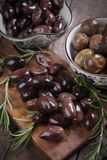 Cured greek olives. Cured, pickled or brined olive fruit on wooden table Stock Photography