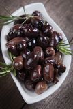 Cured greek olives. Cured, pickled or brined olive fruit on wooden table Stock Photo