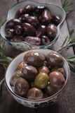 Cured greek olives. Cured, pickled or brined olive t on wooden table Royalty Free Stock Image