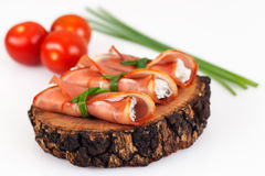 Cured pork loin stuffed with cheeses and olives decorated with chives and cherry tomatoes Isolated on white background. Horizontal shot Royalty Free Stock Photos