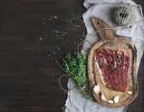 Cured pork meat prosciutto on a rustic woodem board with garli Royalty Free Stock Image