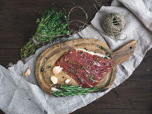 Cured pork meat or prosciutto on a rustic woodem board with garli Royalty Free Stock Photo