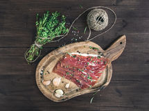 Cured pork meat (prosciutto) on a rustic woodem board with garlic, spices and thyme Royalty Free Stock Photos