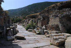 Curetes Street in Ephesus. Beginning of Curetes Street in the ancient town of Ephesus in Turkey with residential area on the hill in the background Royalty Free Stock Images