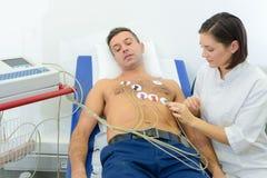 Curi attaccare i cuscinetti del monitor di cuore sul paziente immagine stock