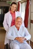 Curi con l'uomo senior in sedia a rotelle Fotografia Stock