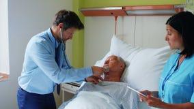 Curi facendo uso della compressa digitale mentre medico che esamina un paziente stock footage