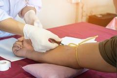 Curi il paziente del sangue di tiraggio dal braccio per salute dell'assegno fotografia stock libera da diritti