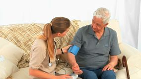 Curi la presa della pressione sanguigna del suo paziente maschio archivi video