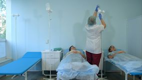Curi nella maschera ed in guanti che preparano il gocciolamento per i pazienti femminili in un reparto Fotografia Stock Libera da Diritti