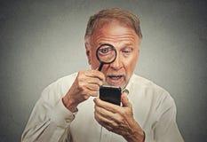 curieux Homme supérieur regardant par la loupe le smartphone Photo libre de droits