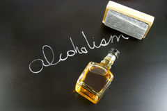 Curing Alcoholism. Blackboard with the word ALCOHOLISM written in chalk with an eraser and a mini bottle of whiskey stock image