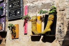 Curiosidades no acre, no Akko, nas botas e nas sapatas, bolsas, como os potenciômetros de flor, projeto exterior e decoração, em  imagens de stock