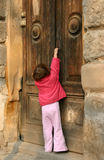 Curiosity. Little girl trying to open the door Royalty Free Stock Photos
