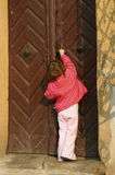 Curiosity. Little girl trying to open the door Stock Photography