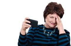 Curiosity and confusion at the same time. Adult mature woman looks at mobile phone screen holding with right hand. Lady feels both curiosity and confusion at the Royalty Free Stock Images