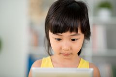 Curiosity. Girl with curiosity expression looking at the tablet royalty free stock photo