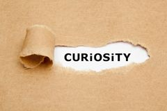 Curiosity Torn Paper Concept. The word Curiosity appearing behind torn brown paper. Curiosity is the desire to learn or know more about something or someone royalty free stock photo