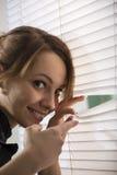 Curiosity. The woman looks through jalousie Stock Image