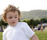 Curious. Young boy outside with curious look on face stock photo