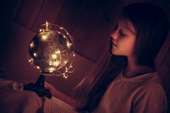 Curious admiring child girl with book in bed looking at shining night earth globe concept curiosity knowledge education developmen stock image