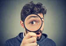 Curious amazed man looking through a magnifying glass. Curious amazed young man looking through a magnifying glass with a big eye royalty free stock photography
