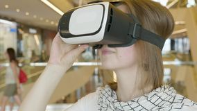 Curious amazed woman trying augmented reality glasses, feeling excited about VR headset simulation, exploring virtual. Life by gesturing hands to touch 3d world stock video