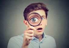 Curious amazed man looking through a magnifying glass Royalty Free Stock Image