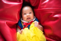 Curious Asian baby with fantasy dress. Portrait of curious cute Asian baby, 3 months old with fantasy outfit costume, on vibrant red bean bag. Adorable beautiful Royalty Free Stock Image