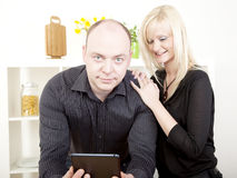 Curious wife reading her husbands tablet. Curious attractive young blonde women reading her husbands tablet over his shoulder, as he looks up at the camera, with Royalty Free Stock Images